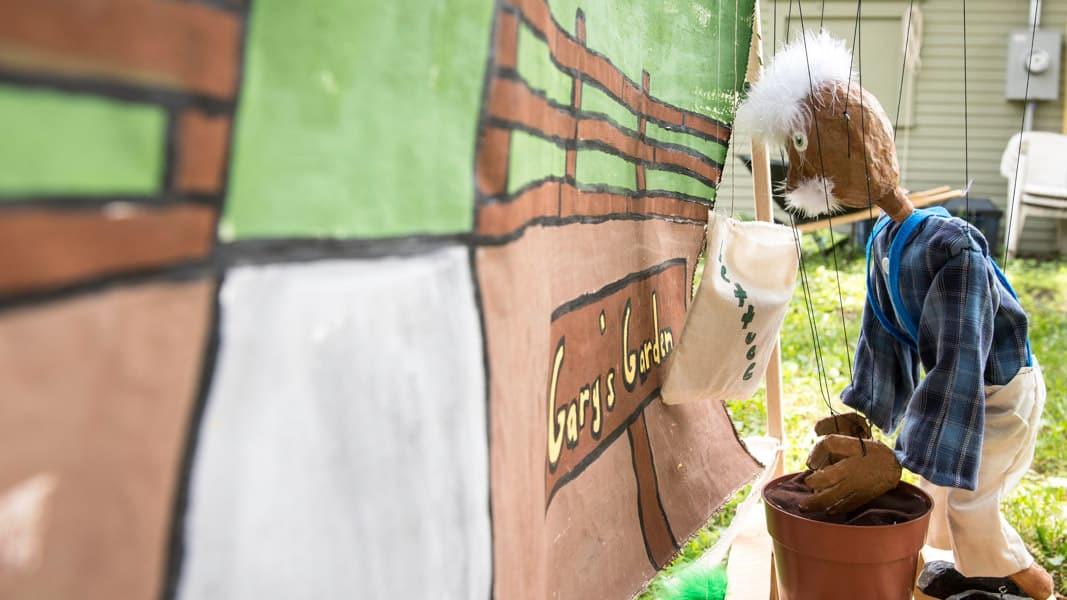 gardener marionette agains a garden backdrop.