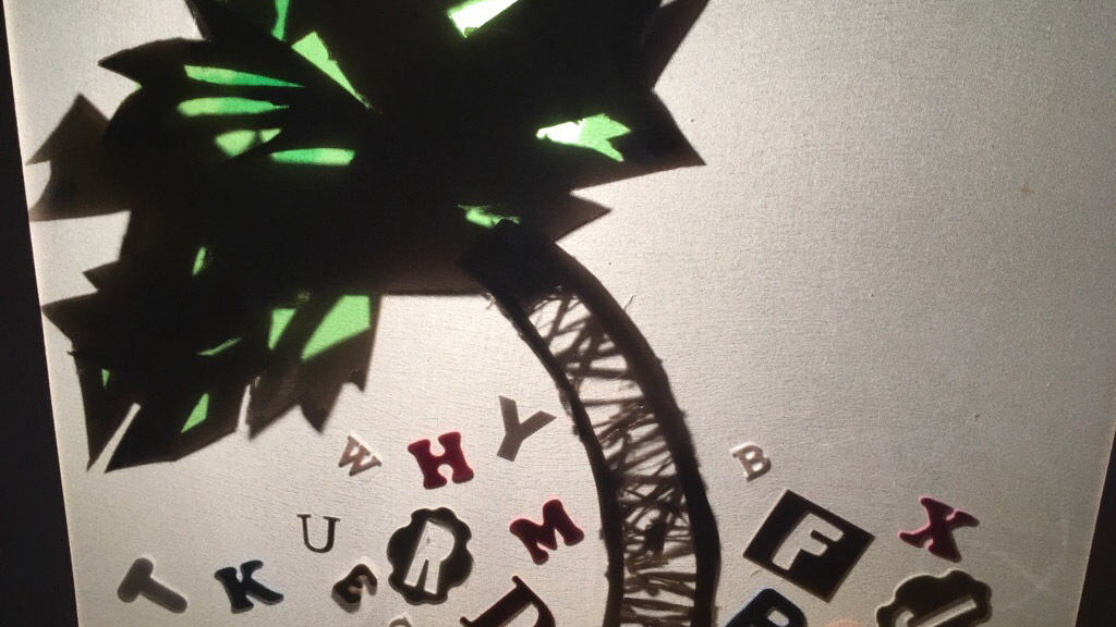 letters under a shadow puppet coconut tree.